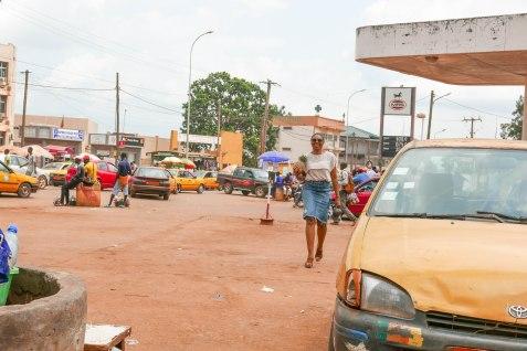 Josette hat Ananas erstanden. Die gelben Autos sind die Taxis. Vermutlich endet jeder Toyota dieser Welt irgendwann einmal als Taxi in Yaoundé oder anderswo in Afrika.