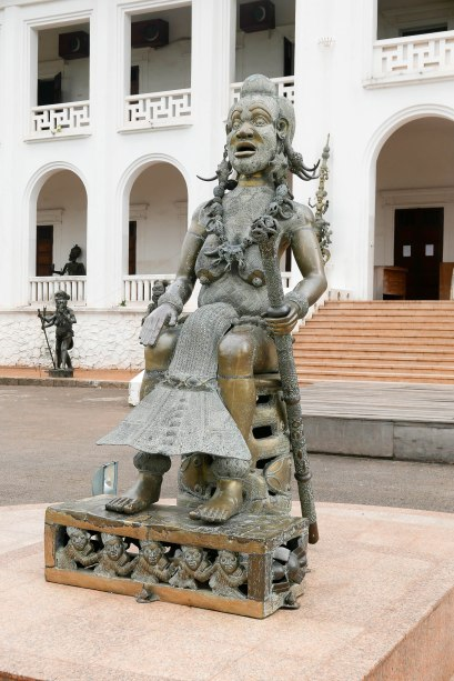 Diese Skulptur bezieht sich auf die Sage einer der ersten und wenigen weiblichen Herrscherinnen im Westen Kameruns. Sie wurde ins Meer gestoßen, konnte aus diesem aber, nun mit einem Fischschwanz, entsteigen und herrschte seitdem auch über das Meer.