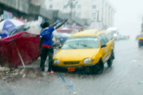 Der Taxifahrer hat im Regen das Schlagloch übersehen. Die beiden Gesellen daneben sind ihm für ein Trinkgeld gern behilflich, den Wagen zu befreien, es ist vermutlich ihr Geschäftsmodel.